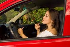 红色汽车的美丽的性感的少妇使用使用后视镜的一支液体桃红色唇膏 库存照片