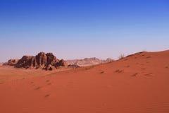 红色沙丘有岩石背景在沙漠 库存图片