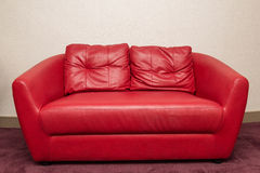 红色沙发在屋子里,白色墙壁 免版税库存图片