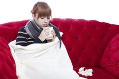 红色沙发的女孩得感冒 免版税库存图片
