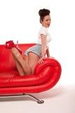 红色沙发的计划评审技术Pinup女孩 免版税库存照片