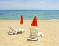 红色沙滩伞和白色躺椅 免版税库存照片