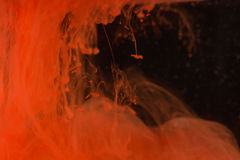红色油漆下落在水中 库存照片