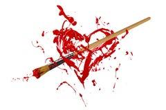 红色油漆刷刺穿的被绘的心脏 库存照片