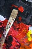 红色油漆和刷子在纸 库存照片