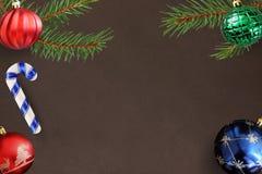 红色波浪,蓝色和绿色有肋骨球,在黑暗的背景的棍子与圣诞节冷杉分支 免版税图库摄影