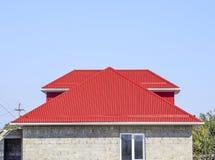 红色波纹状的屋顶 煤渣砌块议院  有波纹状的板料塑料窗口和屋顶的议院  库存照片