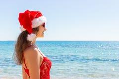 红色泳装和圣诞节帽子的女孩在海滩 复制空间 库存照片