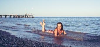 红色泳装的女孩在海滩 免版税库存图片
