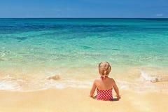红色泳装的女孩坐沙子海滩边缘 库存照片
