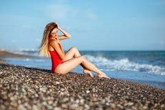红色泳装的年轻长发女孩 免版税库存图片
