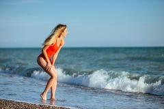 红色泳装的年轻长发女孩 免版税图库摄影