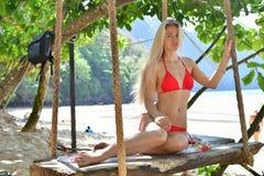 红色泳装的金发碧眼的女人在海滩摇摆 免版税库存照片