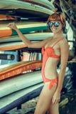 红色泳装的年轻性感的女孩-有水橇板的摆在努沙Dua海滩的,热带巴厘岛,印度尼西亚冲浪者 免版税库存照片
