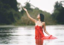 红色浴巾的一名亚裔妇女享受雨和自然在Th 免版税库存照片