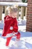 红色海角的小女孩走通过新鲜的雪的 库存图片