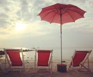 红色海滩床和伞在白色海滩日落 免版税库存图片