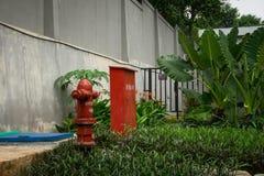 红色消防栓箱子和泵浦在围拢由深堑侧壁照片的后院拍在雅加达印度尼西亚 免版税库存图片