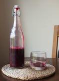 红色液体玻璃瓶桌新鲜的狂放的酒红宝石 免版税库存图片