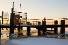 红色温暖的夹克的逗人喜爱的年轻女人看站立在积雪的金属河码头的美好的日出 图库摄影