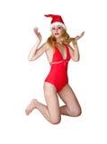 红色游泳衣和圣诞老人一个红色盖帽的美丽的妇女 库存图片