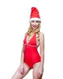 红色游泳衣和圣诞老人一个红色盖帽的美丽的妇女 免版税库存照片