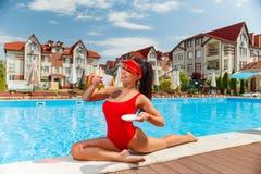 红色游泳衣的女孩在水池附近 免版税库存照片