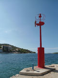 红色灯塔在一个小的克罗地亚港口 图库摄影