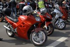 红色炫耀停放的摩托车 免版税库存照片
