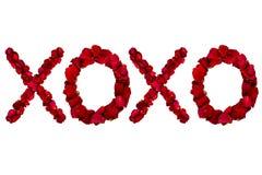 红色烘干了玫瑰花瓣被安排入xoxo 免版税库存图片