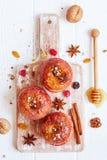 红色烘烤了苹果用桂香、核桃和蜂蜜 秋天或胜利 免版税图库摄影