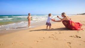 红色照片的母亲给箱子小女孩在海浪的男孩戏剧 影视素材
