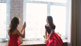红色燕尾服摆在的两个在智能手机的少妇和photograps在窗口 影视素材