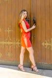 红色燕尾服短小步行的美丽的少妇从老房子 免版税库存照片