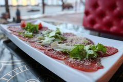红色牛肉和猪肉肉在一块白色长方形板材的开胃菜洒与乳酪和绿色在咖啡馆的一张桌上, 库存照片