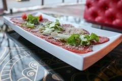 红色牛肉和猪肉肉在一块白色长方形板材的开胃菜洒与乳酪和绿色在咖啡馆的一张桌上 图库摄影