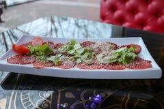 红色牛肉和猪肉肉在一块白色长方形板材的开胃菜洒与乳酪和绿色在咖啡馆的一张桌上 免版税库存照片
