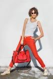 红色牛仔裤的时髦的少妇有袋子的 库存照片