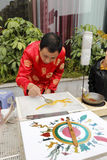 红色特性衣服的民间艺术家做繁体中文糖绘画 免版税库存图片