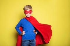 红色特级英雄海角和面具的男孩 超人 在黄色背景的演播室画象 免版税库存图片