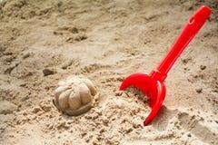 红色玩具桶和被铸造的沙子在沙盒或在海滩,骗局 免版税库存照片
