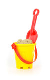 红色玩具铁锹和一个黄色桶 库存图片