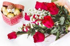 红色玫瑰与巧克力球的花花束 库存照片