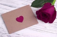 红色玫瑰和一个红色心脏信封 库存图片