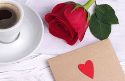 红色玫瑰和一个红色心脏信封 免版税库存图片