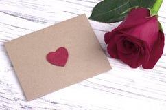 红色玫瑰和一个红色心脏信封 库存照片