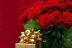 红色玫瑰和与丝带的金黄礼品 库存图片