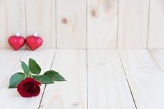 红色玫瑰和两心脏在木背景 免版税库存图片