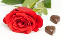 红色玫瑰和各种各样的巧克力形状在白色背景爱言情华伦泰` s天概念 免版税库存图片