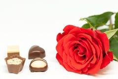 红色玫瑰和各种各样的巧克力形状在白色背景爱言情华伦泰` s天概念 库存图片